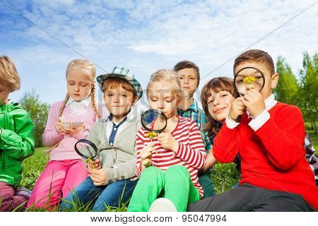 Cute children sit in the meadow with magnifiers