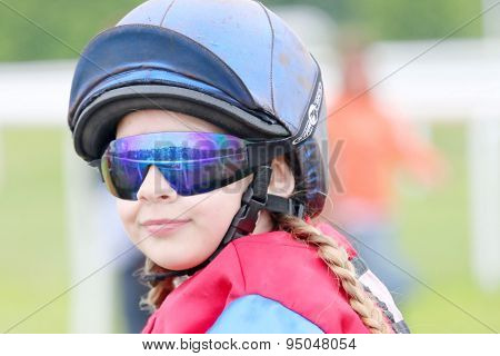 Young Girl Wearing Sun Glasses Sitting On A Pony