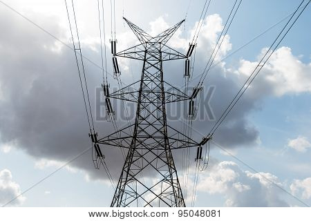 High voltage transmission line tower against a cloudy sky