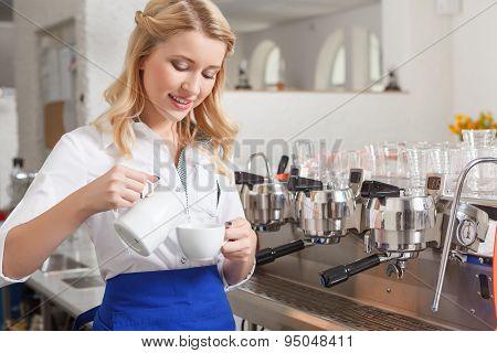 Pretty female barista pouring some milk in cup