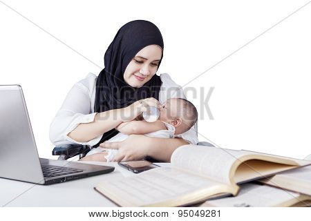 Mother Nursing Baby While Working