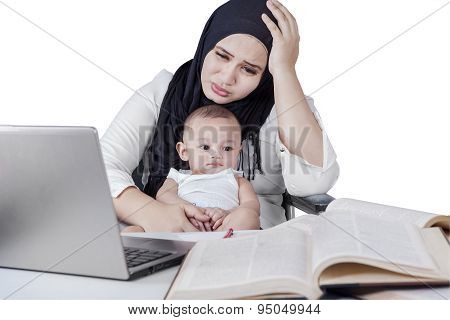 Stressful Young Housewife Working With Her Baby