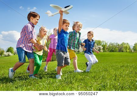 Boy with other kids runs and holds airplane toy