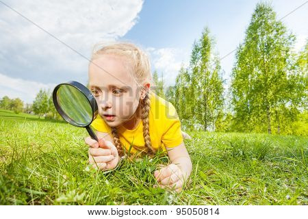 Small girl with magnifier looking through glass