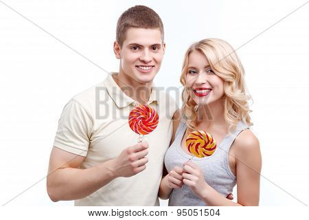 Smiling man and woman with candies