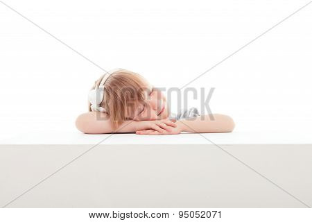 Pretty little girl sleeping  on white surface.