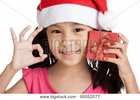 Happy Little Asian Girl Show Ok With Santa Hat And Gift Box