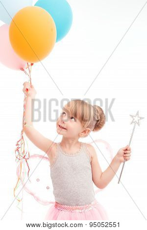 Smiling little girl looking at balloons
