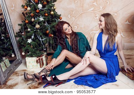 Two friends at the party, girl sitting under Christmas tree