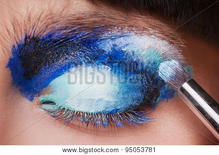 Makeup. Make-up. Painting blue eyeshadows. Eye shadow brush