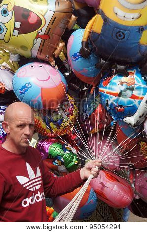 Balloon seller holding colorful balloons