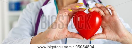 Female Medicine Doctor's Hands Holding Red Toy Heart