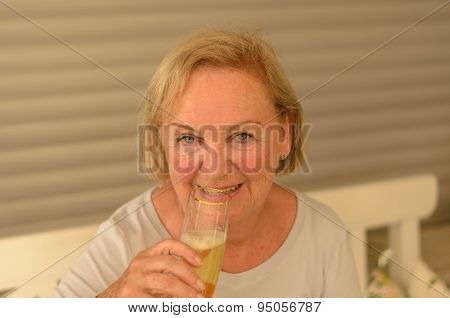 Attractive Senior Lady Drinking Cold Champagne