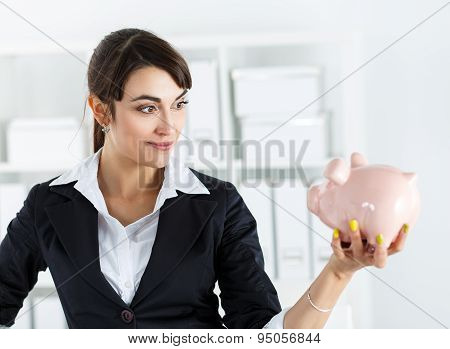 Happy And Mysterious Beautiful Woman Holding Funny Piggybank In Hand
