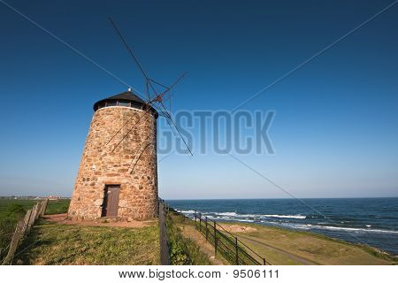 Traditional Scottish Coastal Windmill Under Blue Skies