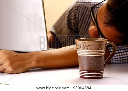 Coffee mug and man sleeping in front of a laptop computer in the background
