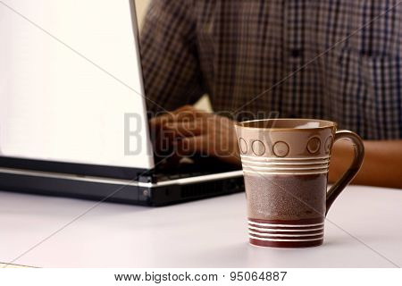 Coffee mug and man working on a laptop computer in the background