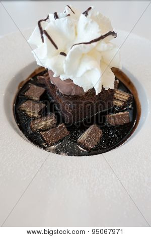 Chocolate fudge cake and ice cream on chocolate sauce and wafer with whip cream on top