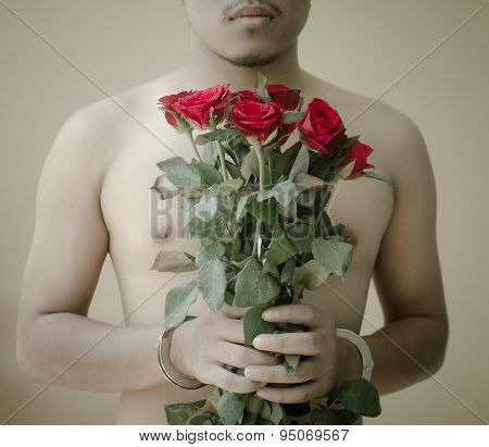 Young Man Holding Red Rose In Hand With Handcuffs