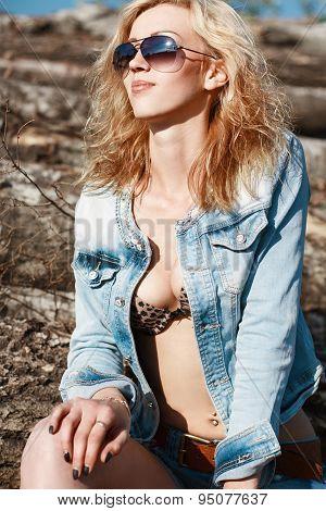 Pretty Woman In A Denim Jacket Sitting On Logs.
