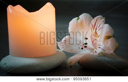 Candle stands on gravel near a flower illuminated candle