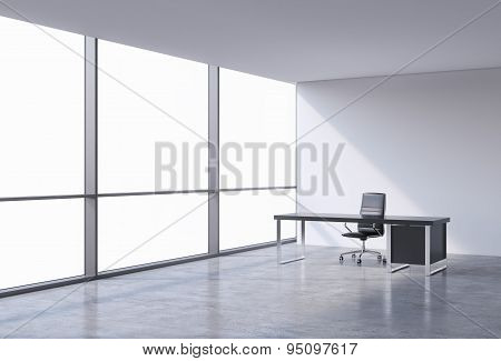 A Workplace In A Modern Corner Panoramic Office, Copy Space On Windows. A Black Leather Chair And A
