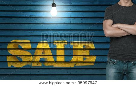Close-up Of A Man In A Grey T-shirt With Crossed Hands. The Word 'sale' On The Wooden Wall.