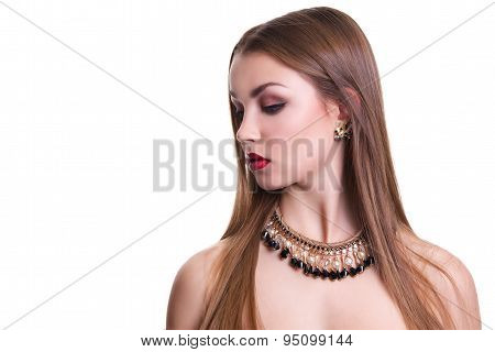 Closeup portrait of a beautiful girl with a black and gold necklace around her neck. Isolated over w