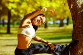 picture of stretching exercises  - A young girl making bodily exercises in autumn park - JPG