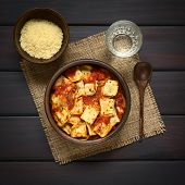 picture of dark side  - Baked ravioli with homemade tomato sauce in rustic bowl with grated cheese in small bowl glass of water and wooden spoon on the side photographed overhead on dark wood with natural light - JPG