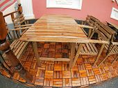 image of distortion  - Wet wooden table and chairs after the rain on wooden floor sidewalk cafe with wide angle distortion view - JPG