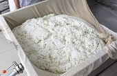 foto of lint  - A woman working in a small family creamery is processing the final steps of making a cheese batch - JPG