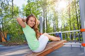 stock photo of crunch  - Girl does crunches on the wooden board at the sports ground during summer sunny day outside - JPG