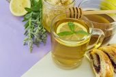 picture of mints  - Cold healthy mint tea with lemon on a table with mint plant honeydipper and dessert - JPG