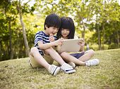 image of playmate  - little asian girl and boy sitting on grass using digital tablet outdoors in a park. ** Note: Shallow depth of field - JPG