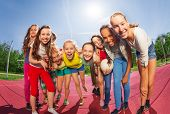 stock photo of volleyball  - Row of teens standing on the volleyball game court holding ball during summer sunny day - JPG