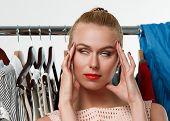 stock photo of wearing dress  - Beautiful blonde woman suffering near wardrobe rack full of clothes choosing dress to wear - JPG