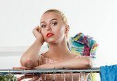 pic of wearing dress  - Beautiful blonde woman suffering near wardrobe rack full of clothes choosing dress to wear - JPG