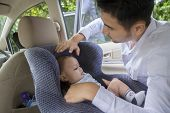 picture of young baby  - Portrait of young man putting his newborn baby on the car seat - JPG