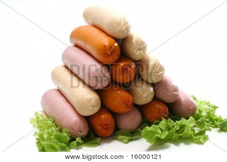 pyramid of raw sausages on lettuce over white