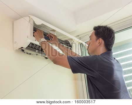 Single electrician man clean fix and maintain air conditioning in the house