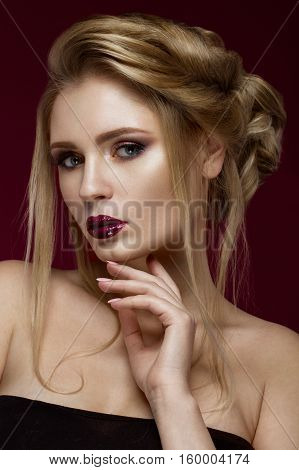 Beautiful blond girl with perfect skin, evening make-up, wedding hairstyle and accessories.Beauty face. Picture taken in the studio.