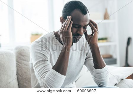 Terrible headache. Young African man touching head with hands and keeping eyes closed while sitting on the sofa at home