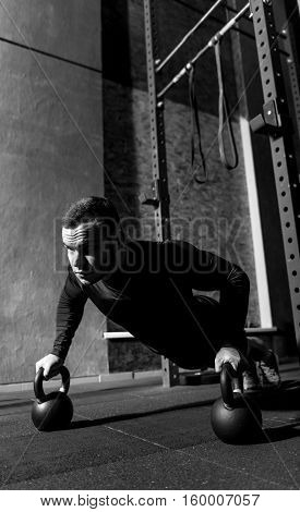 Intensive training. Hard working persistent professional weightlifter doing push ups and focusing on the task while holding kettlebells