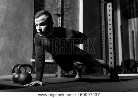 Strong and athletic. Nice persistent young man doing push ups and holding one hand behind his back while developing his muscles