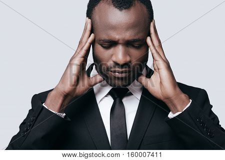 Feeling upset. Young African man in formalwear touching his head with hands while standing against grey background