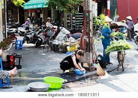 Vietnam, Hue - October 21, 2016: Vietnamese woman washing dishes on the roadside in Hue, Vietnam