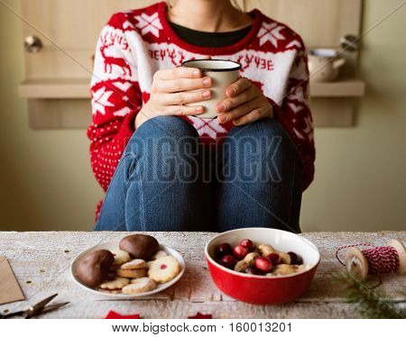 Unrecogiznable woman in red sweater with nordic pattern holding a mug with coffee, cookies, dried fruit and cranberries laid on old wooden table.
