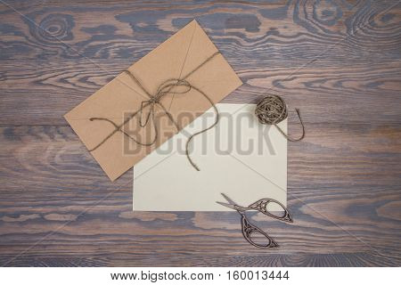 Kraft envelope blank paper twine and vintage scissors on wooden background. Space for your text