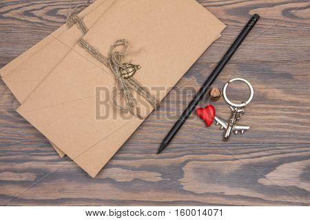 Envelopes tied with twine black pencil and souvenirs from travels on a wooden background. Letters from home